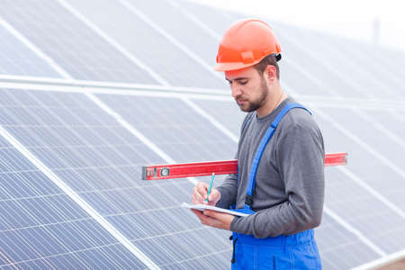 Worker making notes in a notebook on a background of solar panels Stock Photo