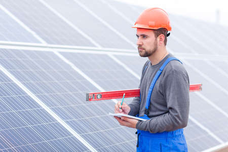 Worker makes notes in a notebook and looks ahead against a background of solar panels Stock Photo