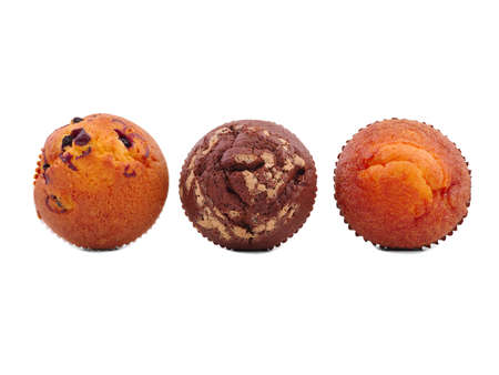 Three cupcakes with different fillings, isolated on a white background, top view, chocolate, with raisins, vanilla, in the middle lies a chocolate cupcake. Stock Photo