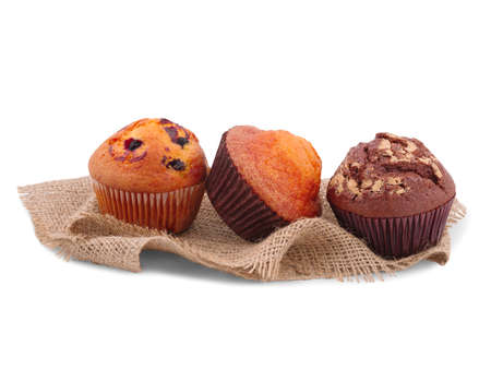 Three cupcakes with various fillings, isolated on a white background, lie sackcloth, chocolate, with raisins, vanilla.