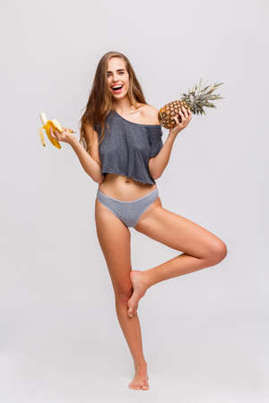 Girl holding a banana and pineapple in hands standing on one leg on a white background Standard-Bild