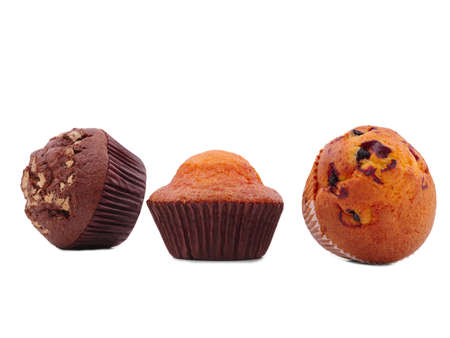 Three cupcakes with different fillings, isolated on a white background, lie on the side, chocolate, with raisins, vanilla, in the middle is a vanilla cupcake. Stock Photo