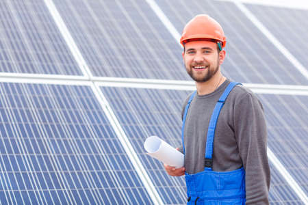 Worker with a paper in his hand and a helmet on his head against a background of solar panels