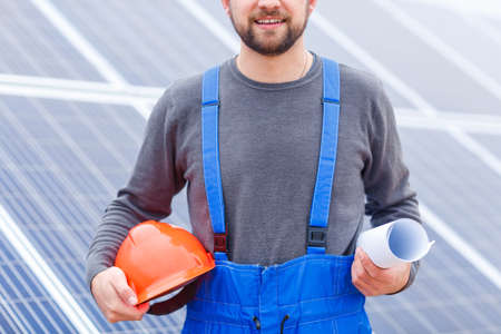 A worker holds a helmet and a paper in his hands close-up on the background of solar panels
