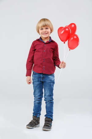 The boy holds balloons on a stick in his left hand against a gray background