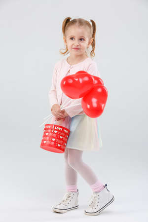 Little girl with balloons and a gift on a gray background