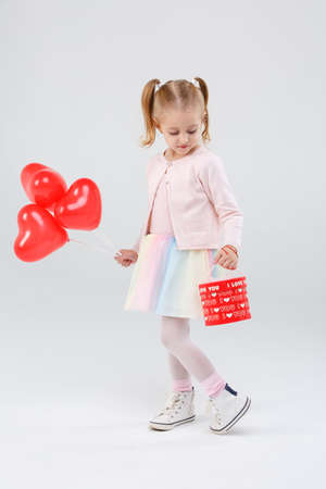 Little girl looks at gift on gray background