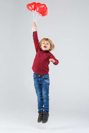 A boy jumping with air balloons on a gray background