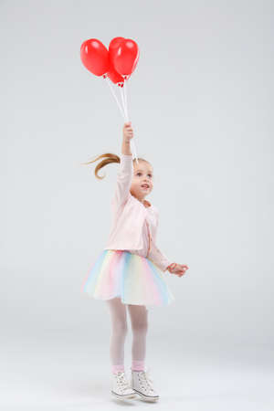 Little girl jumps up with balloons on a gray background Stock Photo