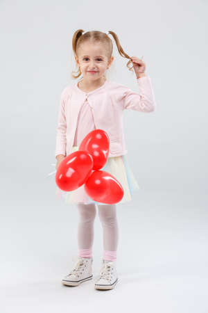 A little girl with balloons on sticks in her hand and holds a pigtail on a gray background Stock Photo