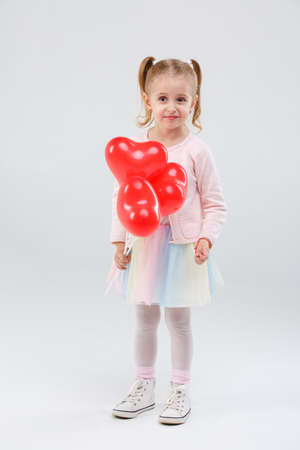 A little girl with pigtails keeps balloons on a stick on a gray background