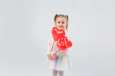 A little girl with pigtails keeps balloons on a stick in front of her on a gray background