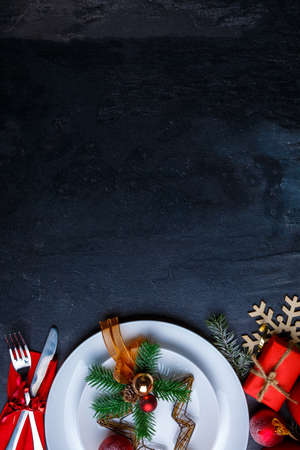 A background with a place for the inscription is decorated with a plate with Christmas decoration and cutlery.