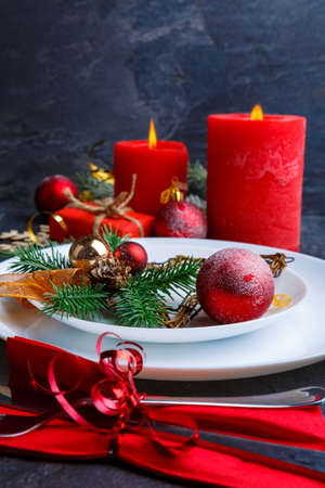 A Christmas table is decorated with candles, Christmas trees and balls. Side view.
