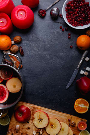 On a surface a pan with mulled wine, a board with apple slices, cranberries, oranges, and burning red candles. Stock Photo