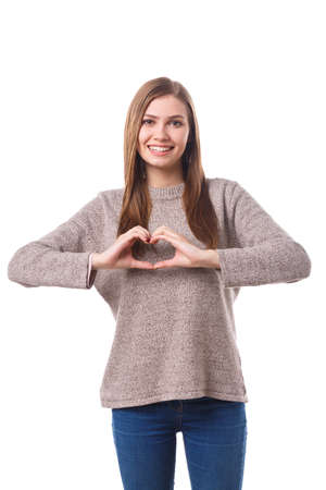 A charming girl showing a gesture of the heart. Isolated on white background.