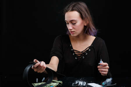 A drug addict girl holding a leather tourniquet and a syringe with a dose of drugs. On a black background.