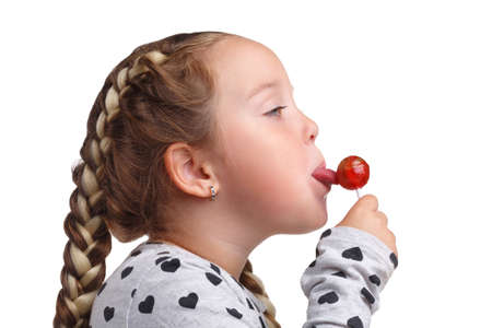 Little girl licking chupa chups close-up on white isolated background