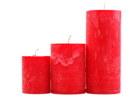 Three different sized red wax candles with a wick, isolated on a white background, stand, all different in height, the concept of holidays, new year, St. Valentines Day