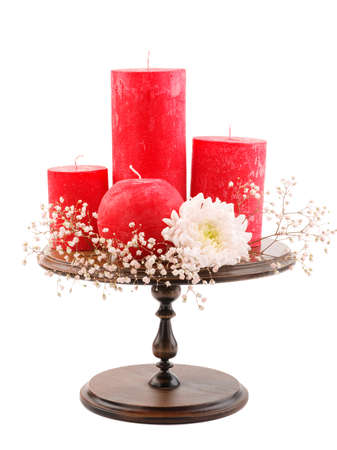 Four different in size and shape, red wax candles with a wick, stand on a wooden candlestick, on an isolated white background, candles next to each other, with small white flowers