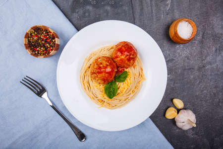 Close-up of spaghetti with grated cheese and meatballs on a black concrete background with garlic, pepper, salt and fork Stock Photo