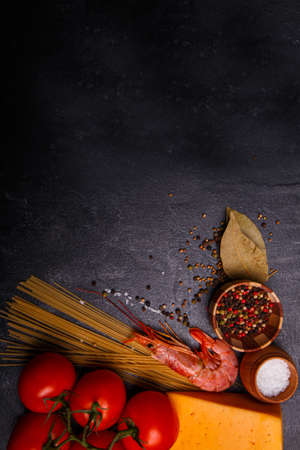 Close-up of cheese, spices, spaghetti, shrimp, tomatoes, on a black concrete background, sprinkled with pepper peas, cooking Italian food, free space for text.