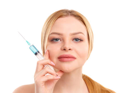 Portrait of a blonde woman isolated on white background, with a syringe in her hands, concept of medicine, plastic surgery. 스톡 콘텐츠