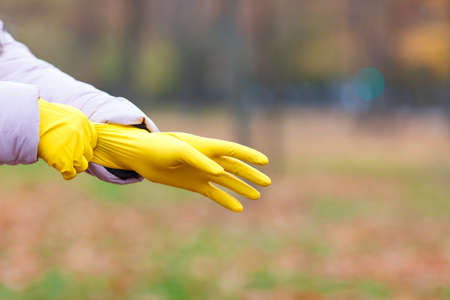 Close-up of a girl in a pink jacket dresses yellow gloves, for cleaning in an autumn park. Stock Photo