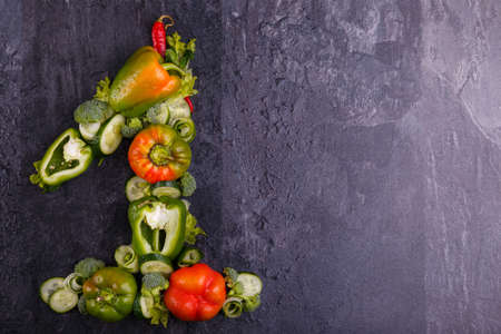 Close-up of appetizing vegetables, lined with one, on the left side, Bulgarian pepper green and red, cucumber and broccoli slots on a black background, free space for text. Фото со стока