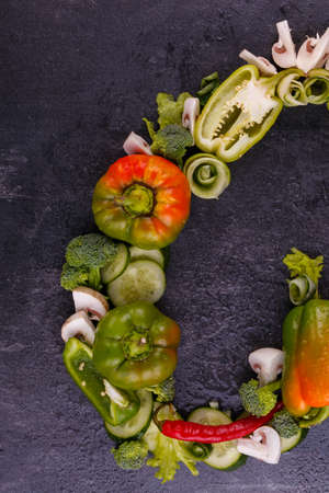 Half of an inverted heart, from juicy, appetizing vegetables, Bulgarian pepper, cucumber, broccoli, laid out on a black background, free space for text, layout
