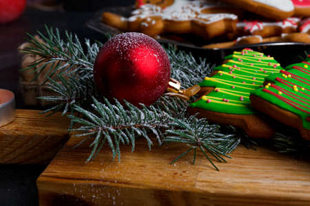 Close-up on a wooden board is a green Christmas tree-shaped biscuit, a red toy ball, a fir branch, a New Years concept, a new year, Christmas. Stock Photo