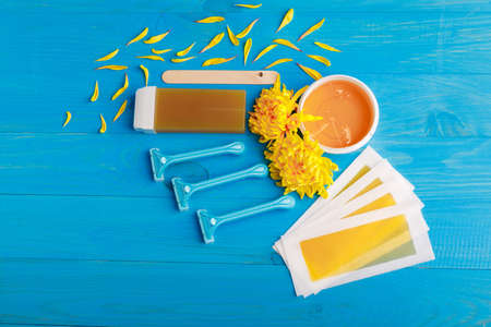 Set for depilation with strips, chopsticks, wax in a cup and wax in a cassette and a row of razors with chrysanthemums on a blue wooden background. View from above Archivio Fotografico
