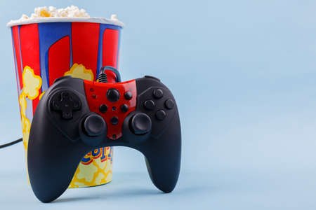 Joystick black with a red center stands at the bowl with popcorn close-up on a blue background Stock Photo