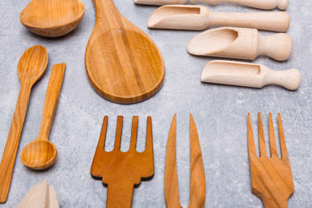 Set of wooden different spoons, forks, stingy appliances on a gray background Stock Photo