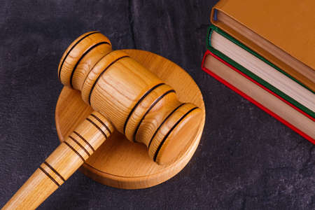 The judges wooden hammer lies on the stands next to a stack of books of different colors on a stone background. Side view close-up Stock Photo