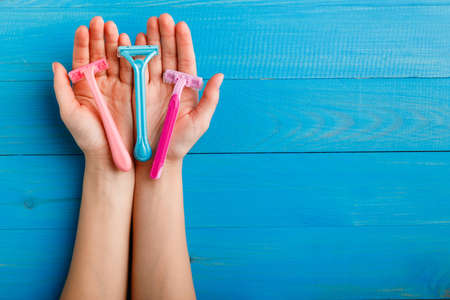 Shaving machine for women of different colors on the palms of the left on a blue wooden background