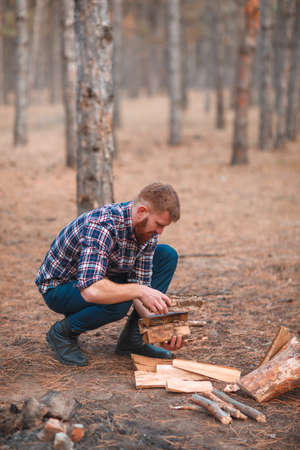A man collects a heap of firewood in an forest. Outdoors.