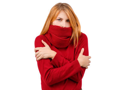 A frozen girl in a sweater and is wrapped in a scarf, it is worth hugging herself with hands. Isolated .