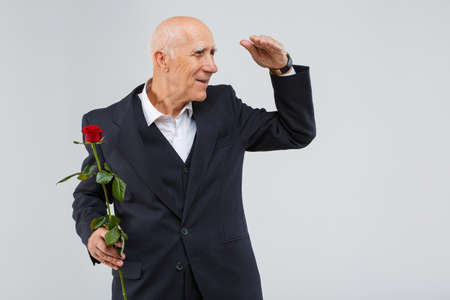 A elderly man, holding one red rose and looking out for someone from afar. Isolation. Imagens