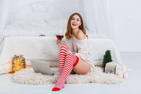 幸せな若い女の子は、寝室、かわいい笑顔とワインのガラスを保持している床に座っています。屋内で。