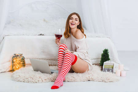 Happy young girl, sits on the floor in the bedroom, cute smiling and holding a glass of wine. Indoors.