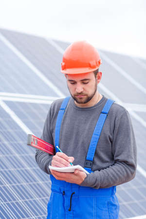 A solar station worker, holds a waterpas in his hands and writes something into a notepad.