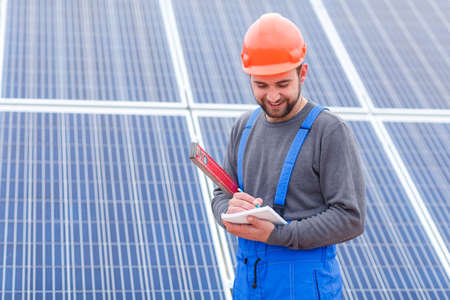 A solar station worker, writes something in a notebook holding waterpas in his hands.