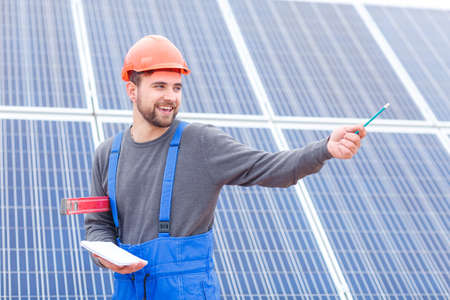 A young worker at the solar battery station in uniform shows his hand somewhere and holds a notebook and waterpas. Stockfoto