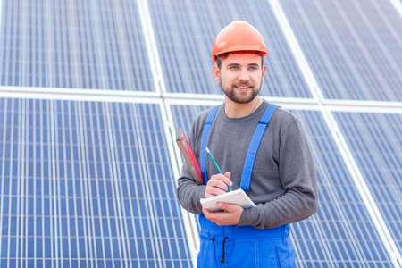 A worker at a solar power station in uniform looks somewhere and writes into a notebook holding waterpas.