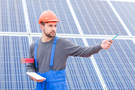 A worker solar cell station holds a waterpas and a notebook and shows a hand somewhere. Outdoors. Stockfoto