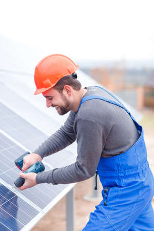 A worker is drills a solar battery panel. Outdoors.