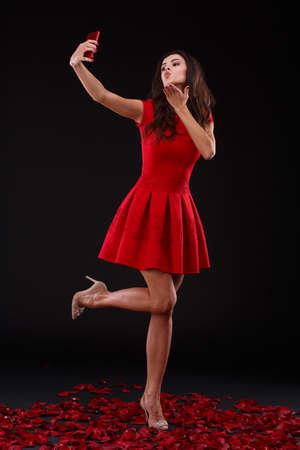 A flirtatious girl in a red dress sends an air kiss and makes selfie. Indoors.