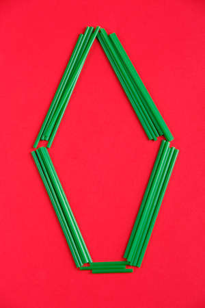 The contrast is green and red. Green plastic cocktail tubes are laid out in the form of a letter O on a red background.