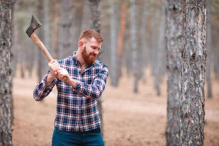 Ein Holzfäller mit rothaarigem Haar und einem Bart schwingt eine Axt an etwas. Draußen. Standard-Bild - 90925761
